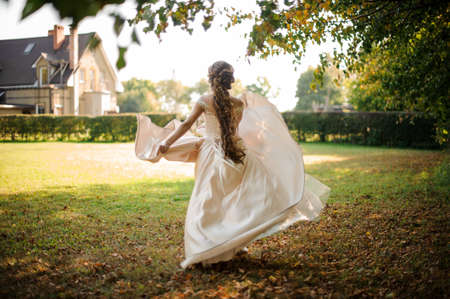 Beautiful bride in a white wedding dress running in the autumn park Banco de Imagens