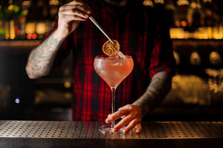 Barman decorating sweet alcoholic cocktail with a slice of dry orange on the bar counter