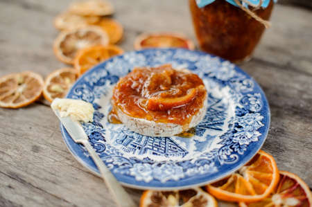 Delicious orange jam on the bread served on the blue ornate plate near the glass jar and dried oranges