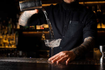 Tattooed bartender pouring an alcoholic drink from the steel shaker to the empty cocktail glass on the bar counter