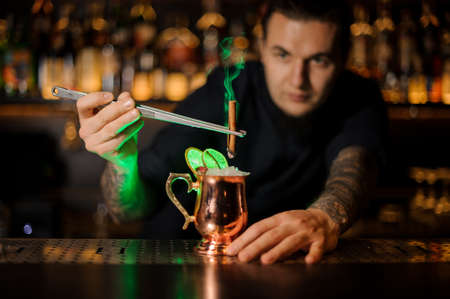 Male bartender adding to a cocktail in the cooper glass with a dried orange aromatic smoked cinnamon with tweezers on the bar counter