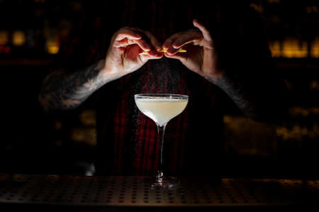 Bartender adding orange zest juice to a Courpse Reviver cocktail in the glass on the bar counter