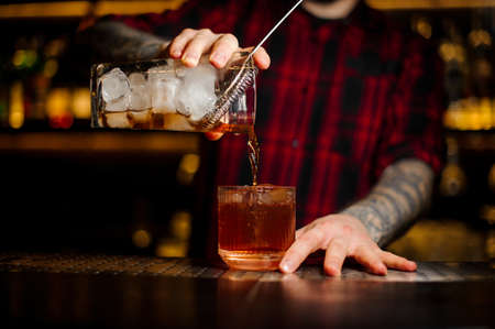 Bartender pouring a Old Fashioned cocktail from the measuring cup with strainer to a glass on the bar counter