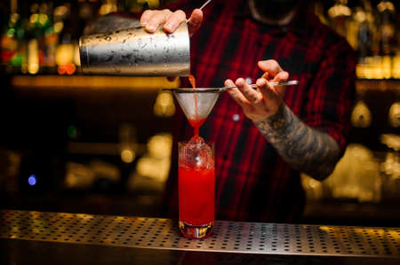 Bartender pouring a Hurricane Punch cocktail from the steel shaker through strainer on the bar counter on the blurred background