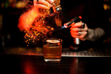 Bartender adding to a cocktail spice and flame it