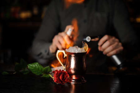 Professional bartender spraying on the delicious cocktail in the golden cup and flaming it with a burner Stock Photo