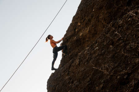Girl equipped with a rope climbing on the sloping rock