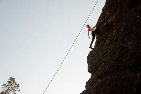 Girl equipped with a rope climbing on the sloping rock and looking down
