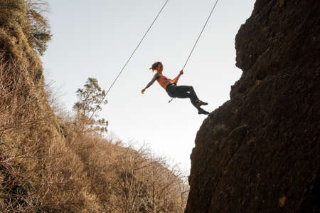 Girl equipped with a rope abseiling on the sloping rock