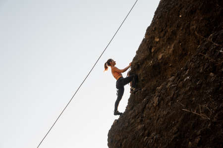 Woman equipped with a rope climbing on the sloping rock