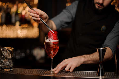 Professional bartender adding to a delicious cocktail red slice decor