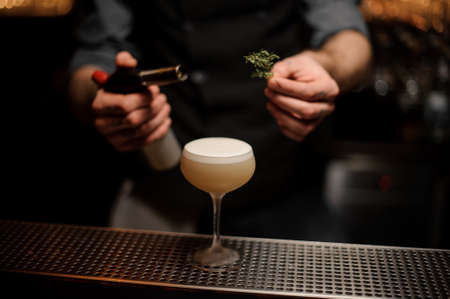 Bartender adds rosemary in alcohol light brown cocktail