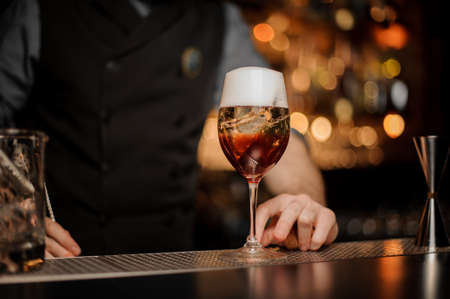Bartender pours cocktail with aperol and sparkling wine Standard-Bild