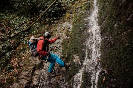 Young man dulfers down the mountain with waterfall in Adjara