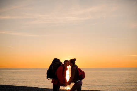 Couple with a backpacks standing near the sea in the sunset holding hands and kissing