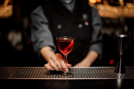 Bartender girl serving a transparent red cocktail in the glass decorated with a lemon zest on the steel bar counter on the steel bar counter in the blurred dark background.
