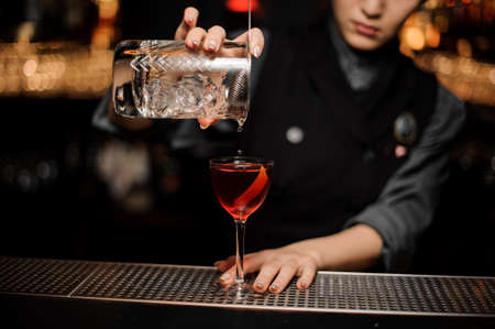 Professional female bartender pouring an alcohol from the measuring glass cup through the strainer to the cocktail on the bar counter in the dark blurred background. Stockfoto