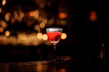 Delicious red cocktail in the glass standing on the bar counter in the blurred background Standard-Bild