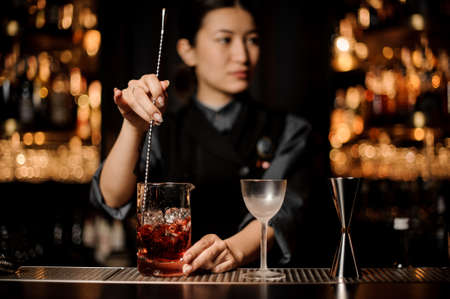 Bartender girl stirring a delicious cocktail with a steel spoon in the measuring glass cup on the bar counter in the dark blurred background Reklamní fotografie