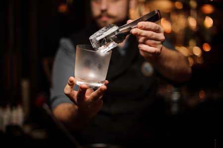 Professional bartender holding in hand an ice cube in tweezers putting it on the a cold matte cocktail glass Stockfoto