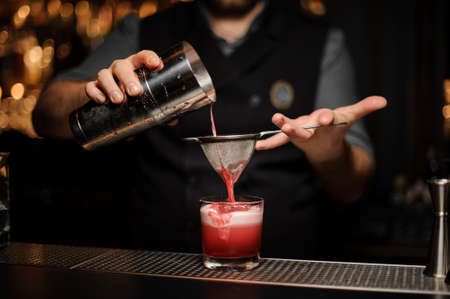 Professional bartender pouring a smooth pink cocktail through the sieve to the glass with one big ice cube Stockfoto