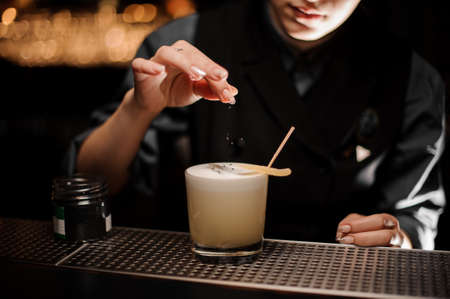 Bartender pours cocktail and adding the ingredients 写真素材