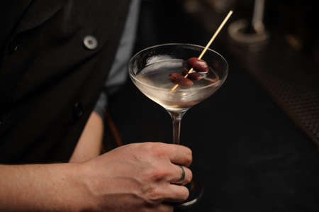 Close shot of alcohol cocktail with olives in bartenders hand Stockfoto