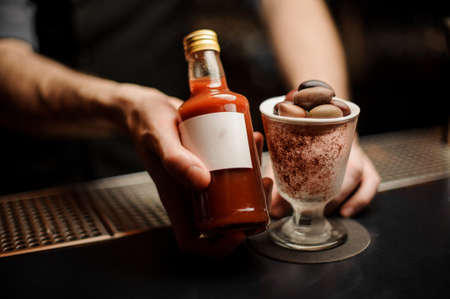 Close-up of bloody mary cocktail bottled in bartenders hands