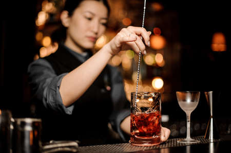 Bartender stirring alcohol cocktail with a bar spoon