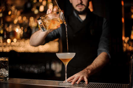 Male bartender makes alcohol cocktail using glass with strainer Standard-Bild