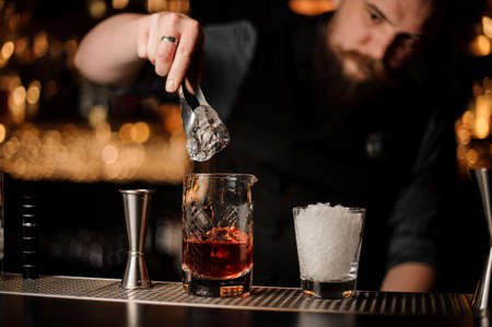 Bartender adds ice in glass with special ice tongs 免版税图像