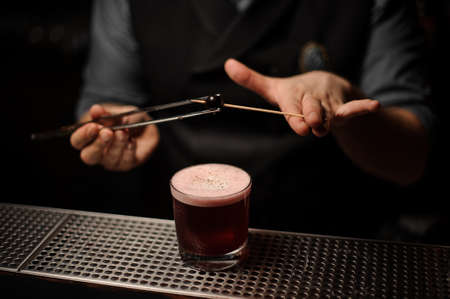 Bartender putting cherry on toothpick with forceps