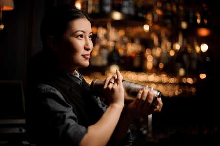 Portrait of female bartender holding shaker at bar counter