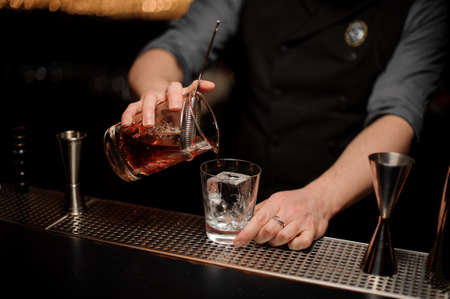 Close shot of young male bartender pouring alcohol cocktail using glass with steel strainer