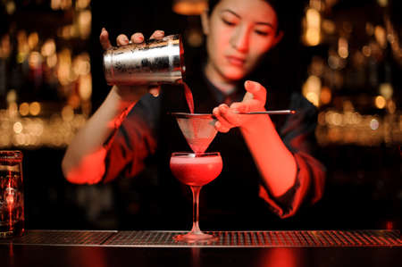 Bartender pouring cocktail using shaker and sieve highlighted in red