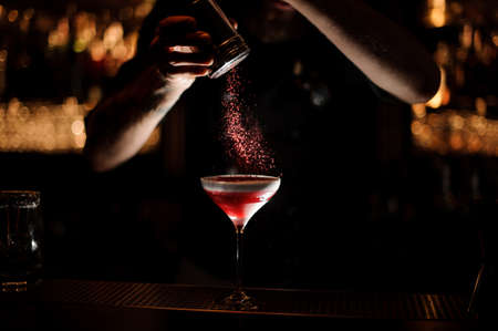 Male bartender sprinkles alcohol cocktail in a glass Stockfoto