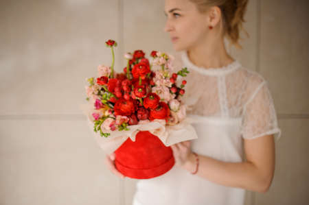 Young girl holds red hat box with flower bouquet