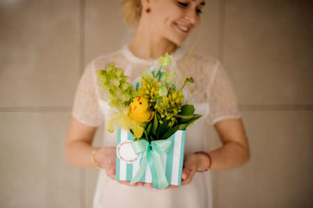 Girl holds striped hat box with flowers and smiles Reklamní fotografie - 122777542