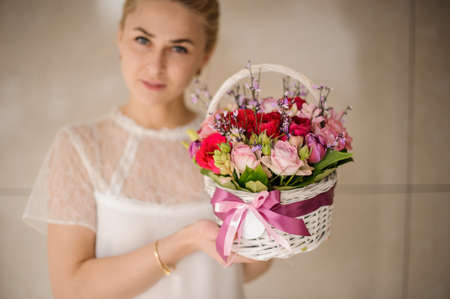 Young girl holding small basket with flowers Reklamní fotografie - 122777546