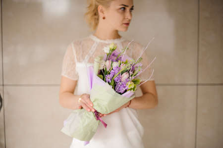 Attractive girl holds bouquet of flowers and smiles Reklamní fotografie - 122777547