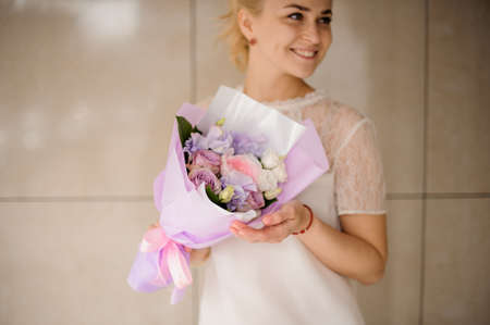 Cute girl holds bouquet of flowers and smiles