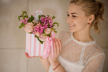 Portrait of girl holding striped hat box with flowers and smiles Stock Photo