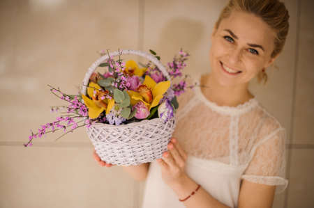 Woman smiles and holds small basket with flowers Stock Photo