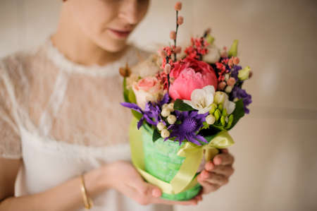 Girl holds small bouquet in a box