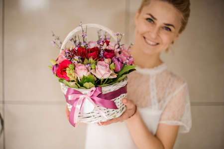 Young girl smiles and holds small basket with flowers