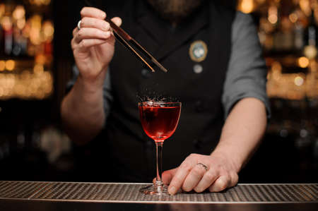 Close-up of bartender adding cherry in alcohol drink Stock Photo