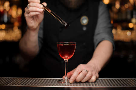 Close-up of bartender dropping cherry in alcohol drink Stock Photo