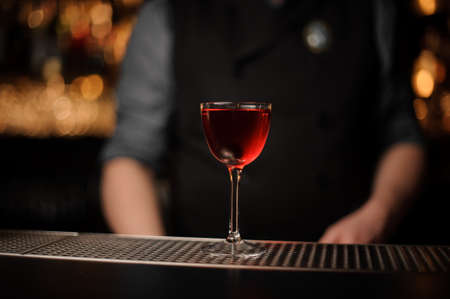 Alcohol drink with cherry with bartender behind