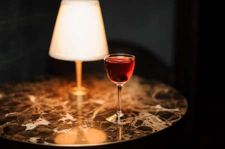 Alcohol drink with cherry on table with lamp Imagens
