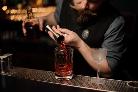Male bartender makes an alcohol cocktail with jigger